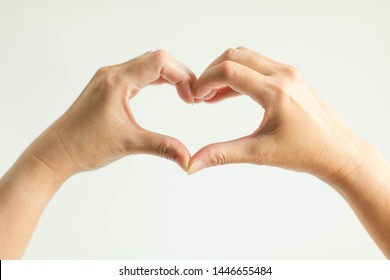 woman show hand signs posturing to heart shape; by splice fingertips together (left thumb with right thumb and left forefinger with right forefinger) on white background; concept of telling love.