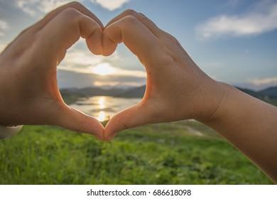 Woman show heart hands, selective focus.