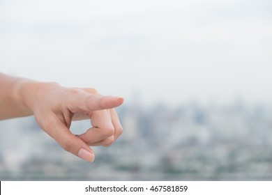 a woman show left side hand show forefinger/index finger, correct, pointing, shoot with blur building in the city background