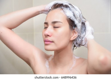 Woman in shower washing hair with shampoo.