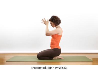 Woman showing  a Anjili Mudra yoga pose on a green mat