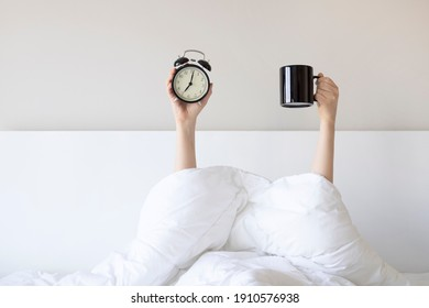Woman showing arm raised up holding coffee cup and black alarm clock behind duvet in the bed room, Young girl with two hands sticking out from the blanket. wake up with fun in morning concept. - Shutterstock ID 1910576938