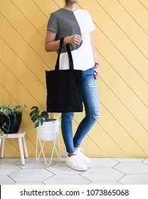 woman showing black totebag. Tote bag mock up for designer. In fun background, pink yellow and green pallete