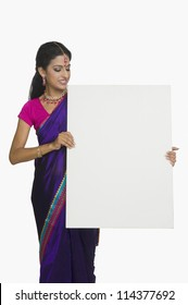 Woman showing a blank placard and smiling