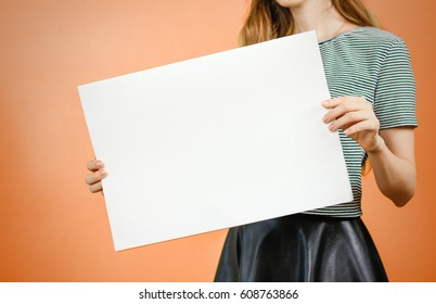 Woman showing blank white big A2 paper. Leaflet presentation. Pamphlet hold hands. Girl show clear offset paper. Sheet template. Booklet design sheet display read first person.