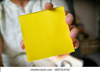 Woman showing a blank yellow sticky note paper. Empty space for your text.