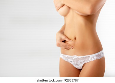 woman showing cellulite on her belly isolated on white background