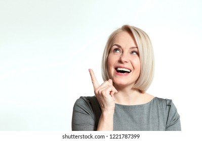 Woman showing at copyspace isolated on white background