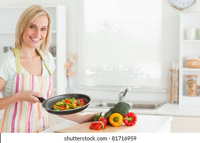 Woman showing cutted peppers in pan in the kitchen