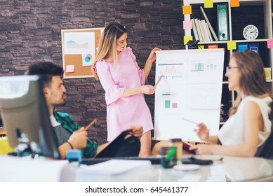 Woman showing diagrams on flipboard to creative team at office