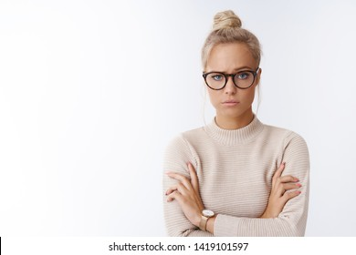 Woman showing disbelief looking suspicious not believing single word crossing arms over chest doubtful raising eyebrow with pokerface standing unimpressed and bothered over white background