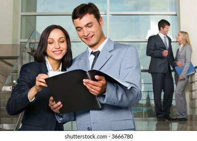 Woman showing documents to her colleague on stairs in the building with glassy walls and couple of talking businesspeople on the background