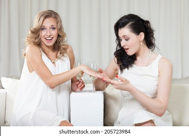 Woman showing engagement ring to her best friend