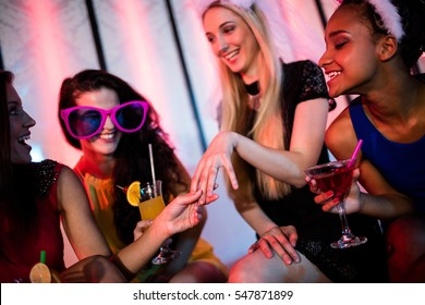 Woman showing engagement ring to her friends at bar