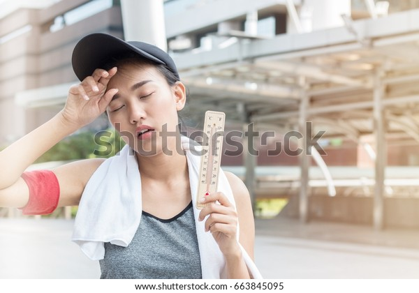 Woman showing facial expression of high temperature. She fell heat stroke.