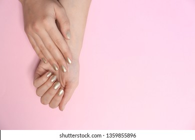Woman showing golden manicure on color background, top view with space for text. Nail polish trends