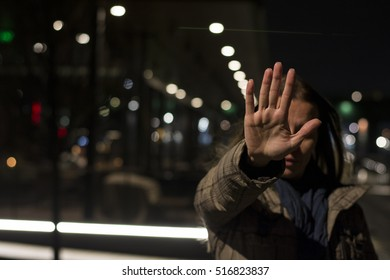 Woman showing hand stop sign while standing at night