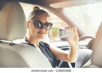 woman showing her new driver license in a car