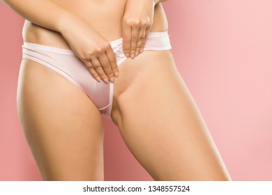 woman showing her shaved pubic area on pink background