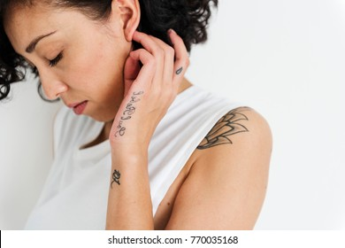 A woman is showing her tattoo on her body