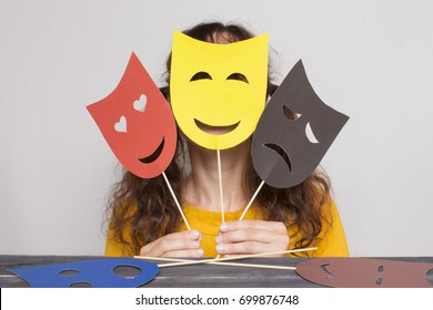 Woman showing masks with different emotions.