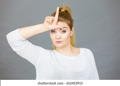 Woman showing mean sign, lame or loser gesture with L fingers on forehead, grey background.