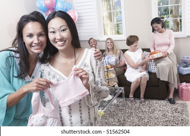 Woman showing off gift at baby shower