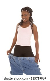 A woman showing off her healthy life by holding out her big pants.