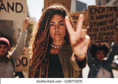 Woman showing a peace sign during protest. Woman with group of females protesting outdoors on city street.