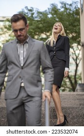 Woman showing power over man in business setting outdoors