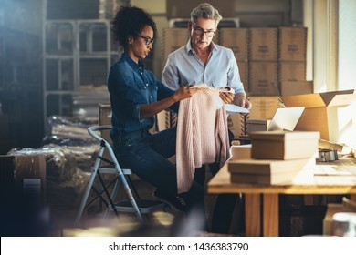 Woman showing the product to her partner before packing and delivering to the customer. Online selling business partners working together in the office.