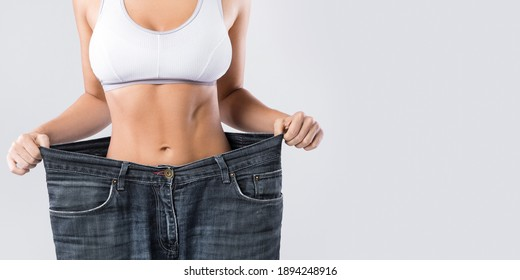 Woman showing result after weight loss wearing on old jeans on gray background