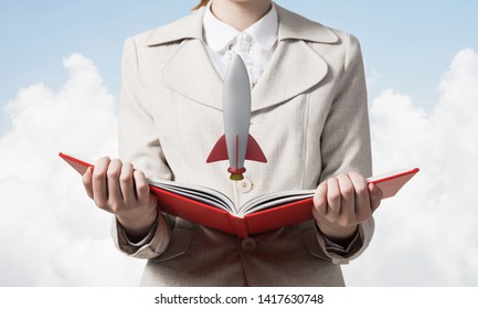 Woman showing rocket ship on open book. Rocket launch as symbol startup company. New creative project concept. Woman in white business suit on background of skyscape. Business innovation.