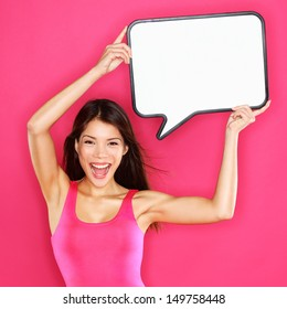 Woman showing sign speech bubble happy sexy with copy space for text. Beautiful excited smiling joyful mixed race Asian / Caucasian female fashion model in pink dress on pink background. Energetic.