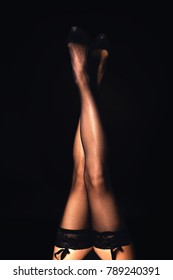 Woman showing slim legs in stockings and black underwear above the black background.