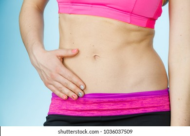 Woman showing some strong abs and flat slim naked belly close up. Part of thin female body. Fit fitness sport girl in sportswear