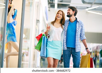 Woman showing something to her boyfriend in the shopping mall