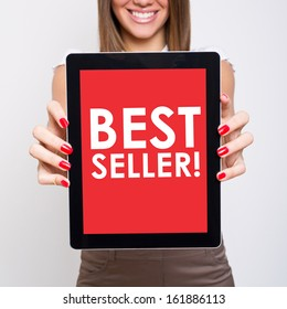 Woman showing tablet computer that states best seller