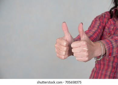 woman showing thumbs up sign in office with copy space.girl dressed in casual clothing. Focus at hands. she giving thumb up as sign of success on gray background. customers feedback concept