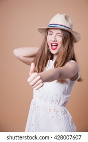 woman showing thumbs up. girl raised thumb up. Funny young woman with hat, studio shot. Beautiful woman in hat on Beige background