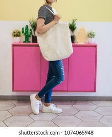 woman showing white totebag. Tote bag mock up for designer. In fun background, pink yellow and green pallete