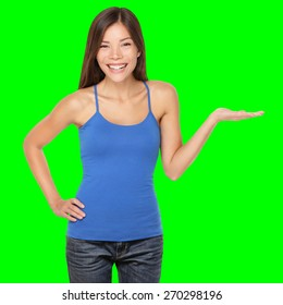 Woman showing your product or message smiling happy Isolated on green screen chroma key background. Beautiful multi-racial girl in blue tank top showing open hand palm.