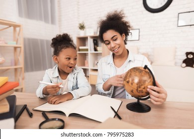 A woman shows a little girl a globe. They look at different countries. Mom helps my daughter to do homework.