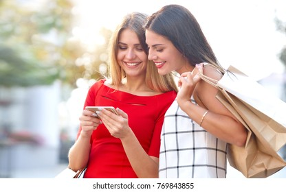 Woman shows on a mobile phone is something to his girlfriend. Happy young women with shopping bags and smartphone on city street