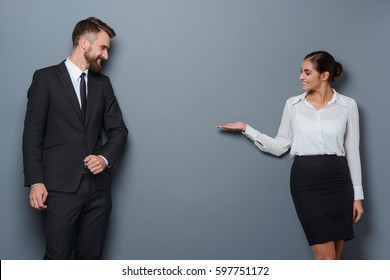 Woman shows something abstract to her business partner. Copy space between two business persons dressed following strict dress-code.