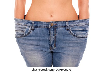 Woman shows that she has lost weight. Big jeans. Isolated on white background.