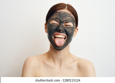 woman shows tongue cosmetic mask made of clay