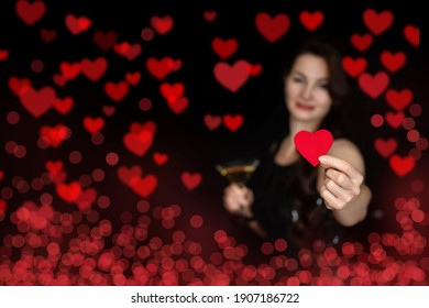 Woman shows a valentine card with a glass in her hands on the background of hearts.