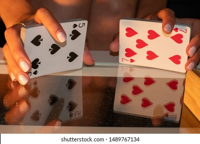 Woman shuffling a deck of cards with a reflection of the hands and cards shown on a glass table