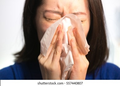 woman sick blows her nose with a tissue